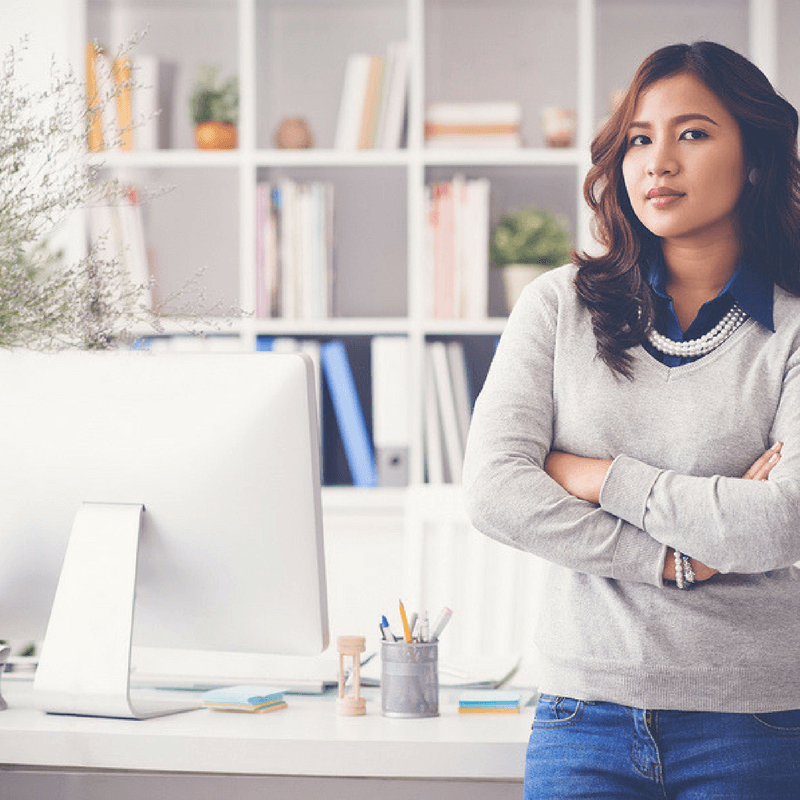 A modern freelancer stands in front of her home office furniture, including an office desk and office storage.