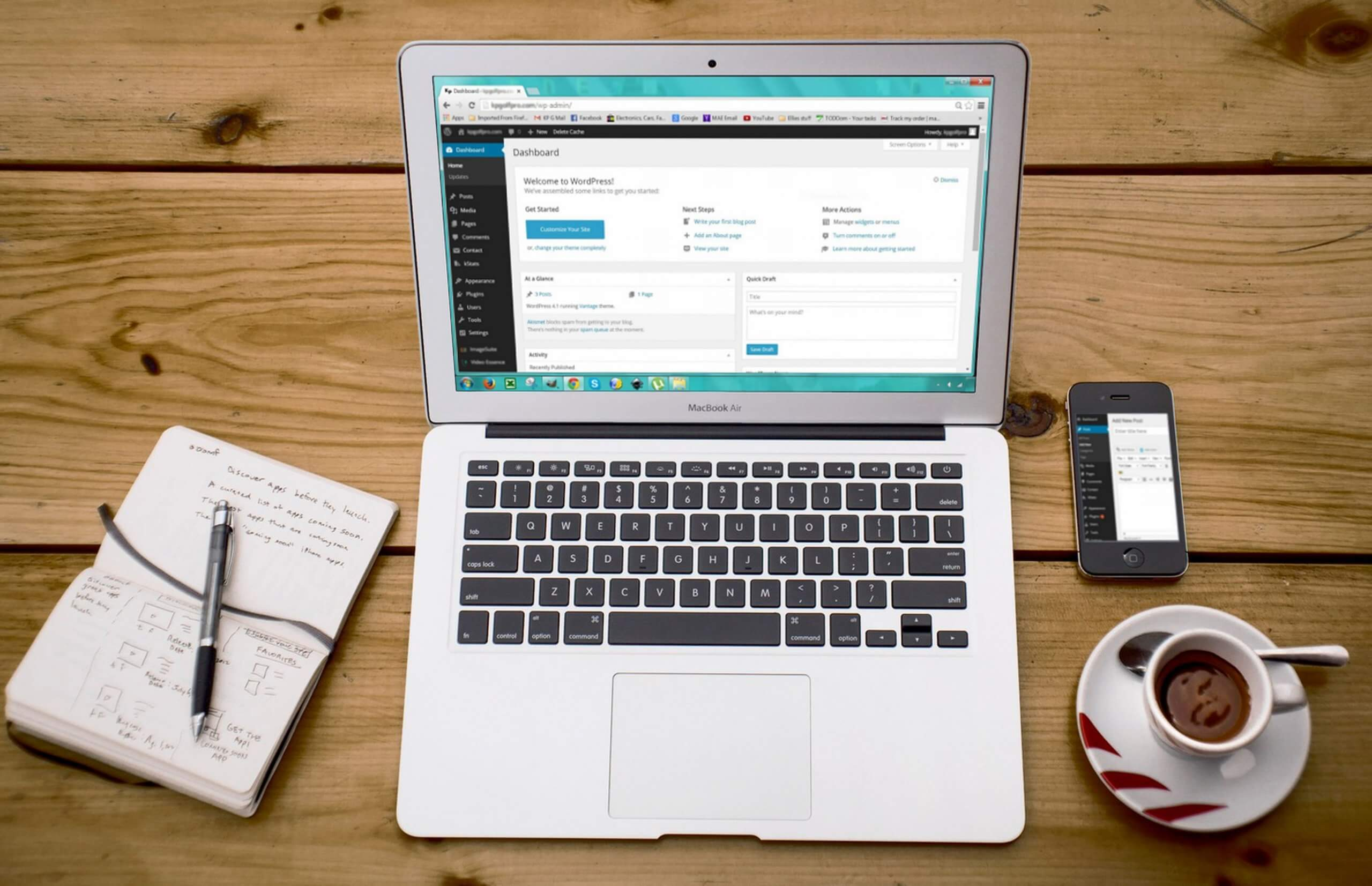 A work area on a wooden table with WordPress loaded up on their Macbook
