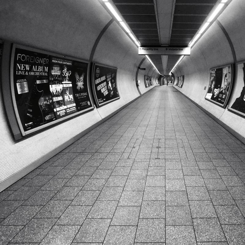 Tube train tunnel with advertising boards on the walls