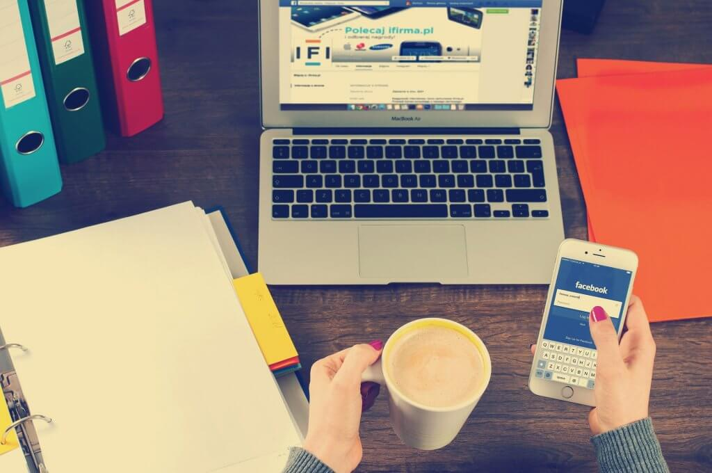 Woman's sat at desk holding cup of coffee and iPhone with Facebook on the screen and laptop in background