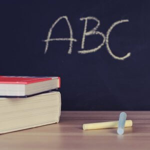 ABC on a chalkboard with two books stacked and some chalk t illustrate a blog by Growtraffic on SEO training