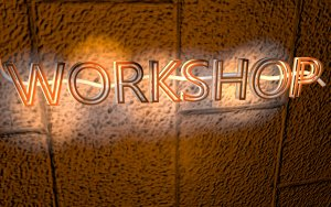 The word Workshop lit up in neon letters on a brickwall to illustrate post by GrowTraffic on SEO training